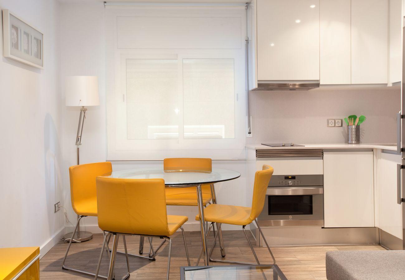 table à manger avec chaises et kitchenette dans un appartement de 2 chambres à Barcelone