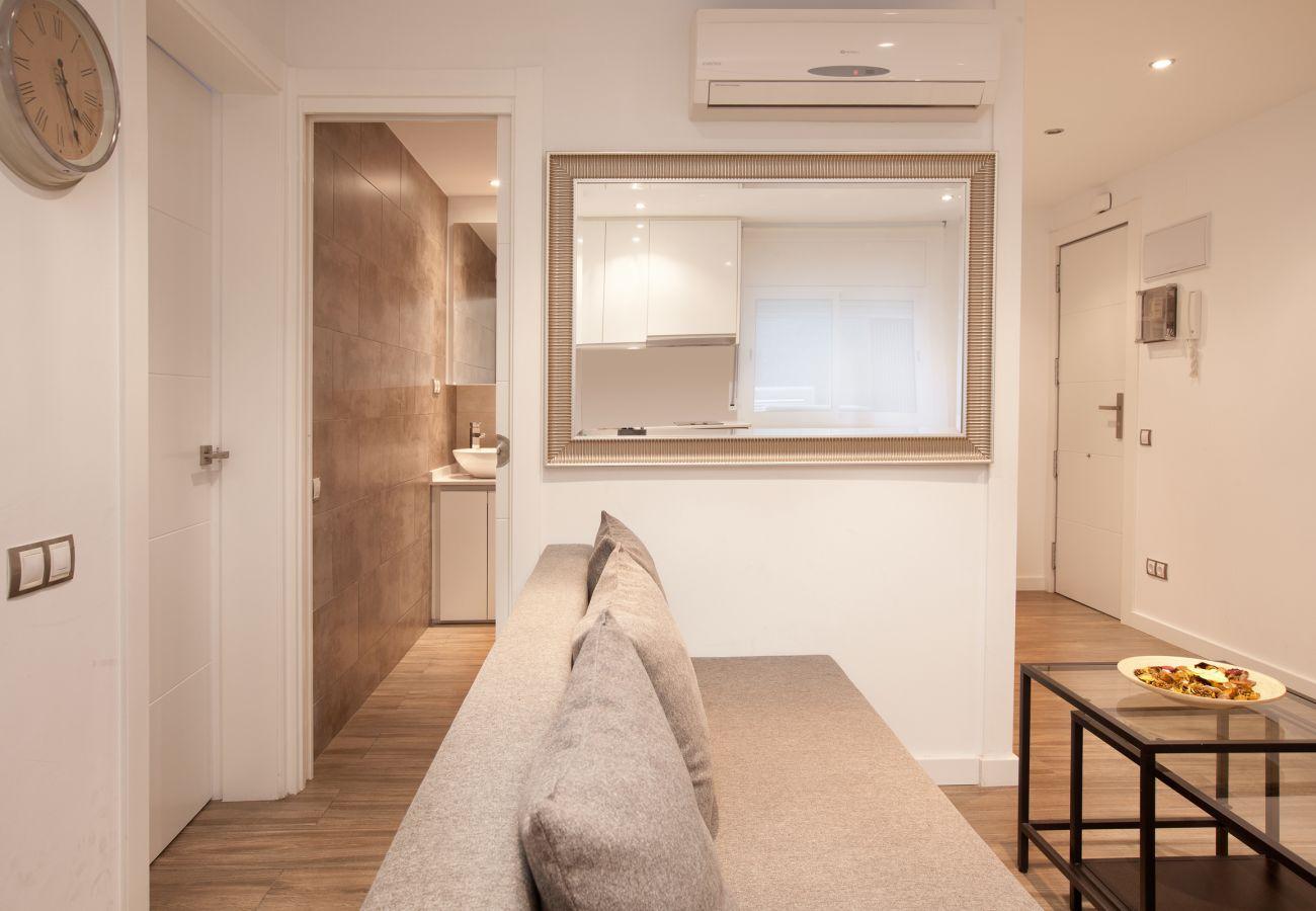 beau salon avec canapé-lit et accès à la salle de bain avec douche à Barcelone près de la Sagrada Familia