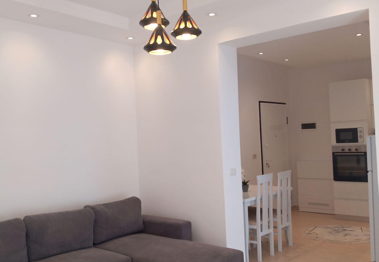 Canapé-lit double dans le salon, cuisine et table à manger dans un appartement d'une chambre à Vlora